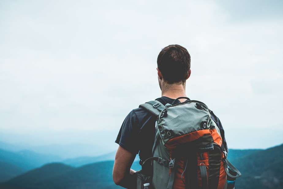 Man carrying rucksack standing high up on a mountain