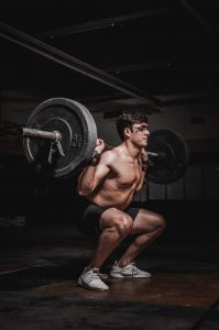 man lifting barbell in a squat position.