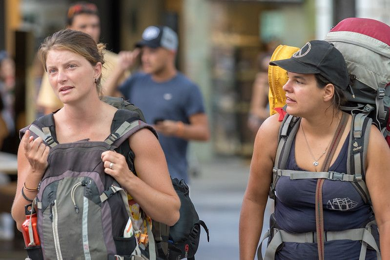 two women who look tired and are carrying multiple backpacks