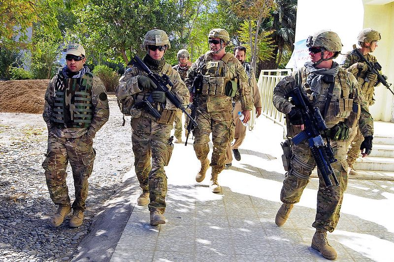 Soldiers walking together in full military gear: what personal items do soldiers carry.