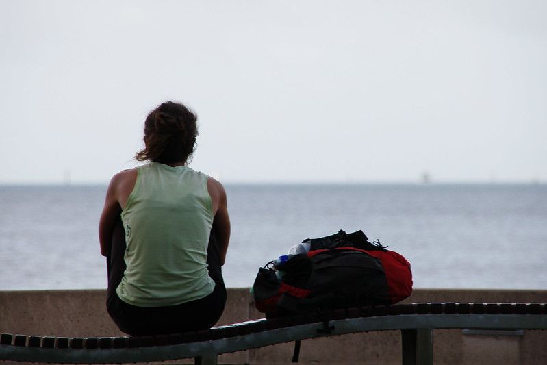 Woman looking out at the water with her rucksack beside her