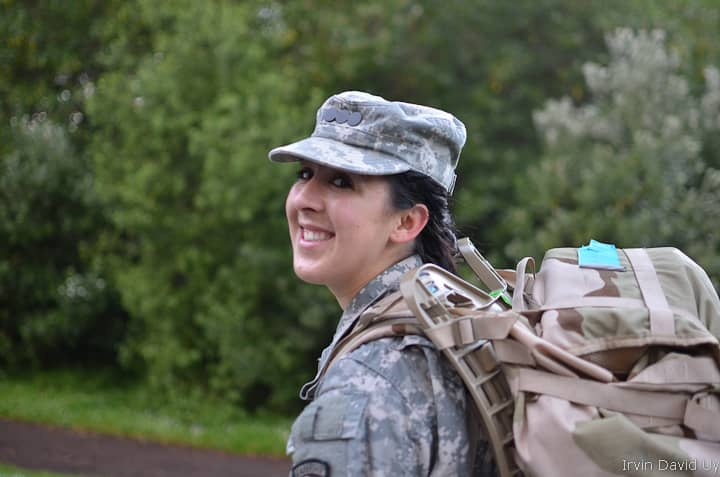 A women in the military rucking while wearing a rucking with an external frame.